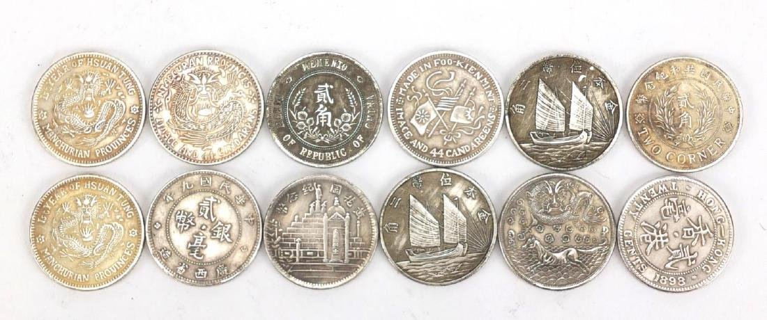 Twelve Chinese silver coloured metal coins including
