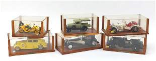 Six model cars housed in wooden display cases including