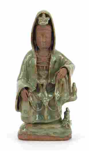 Chinese pottery figure of Guanyin having a celadon