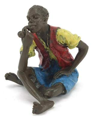 Cold painted bronze figure of a man smoking a pipe in
