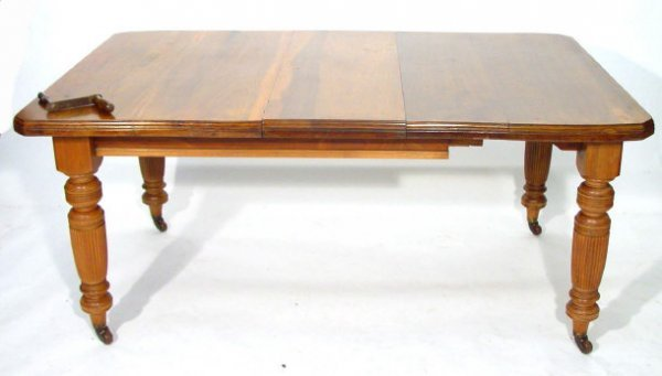 23: Edwardian Walnut wind out dining table with extra l