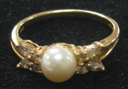 3083: 14K PEARL RING. The ring has a center pearl flank
