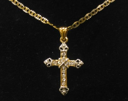 3085: 10K CROSS & CHAIN. The cross is encrusted with wh