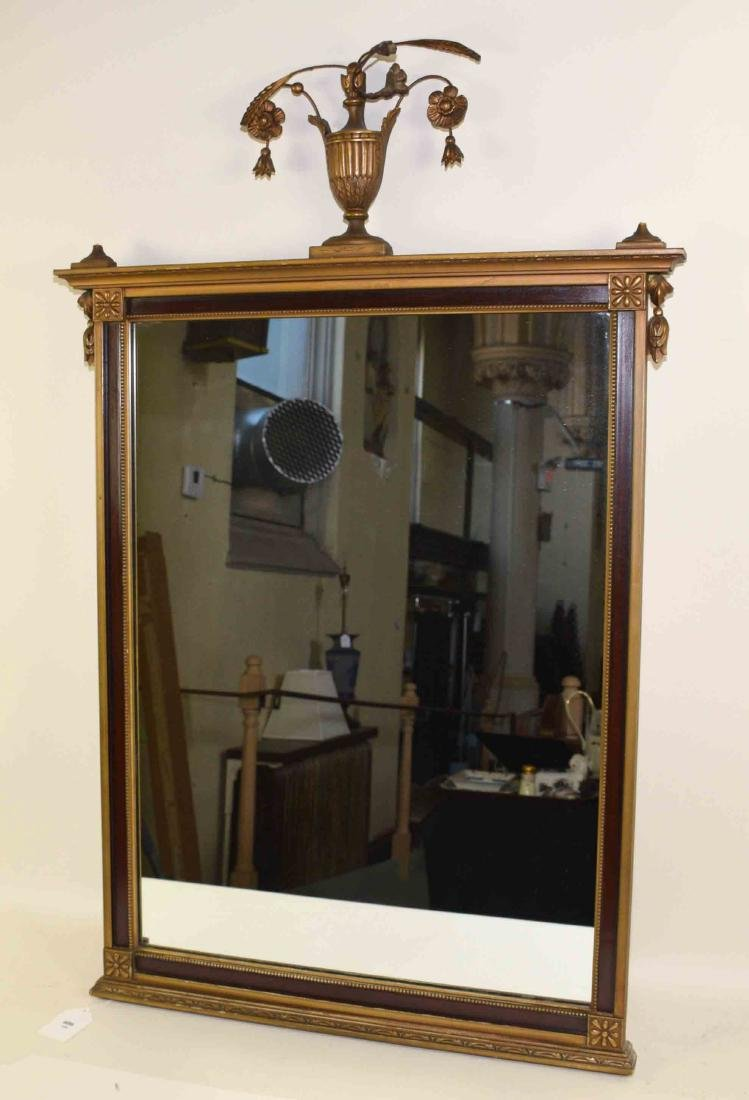 CLASSICAL MIRROR WITH URN WITH FLOWERS ON TOP.