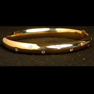 14K DIAMOND BANGLE. The polished gold b
