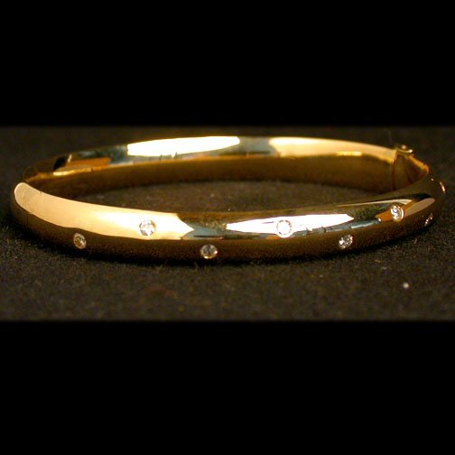 2008: 14K DIAMOND BANGLE. The polished gold b
