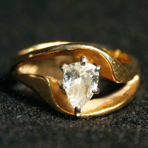 2022: 14K DIAMOND RING. The ring has a pear s