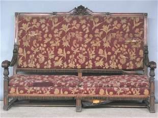 TUDOR STYLE CARVED BENCH. Mahogany frame has lea