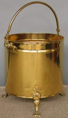 HAMMERED BRASS WOOD BIN. The round bin has a hamm