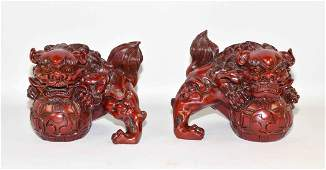 PAIR OF COMPOSITION FOO DOGS - Front paws resting on a