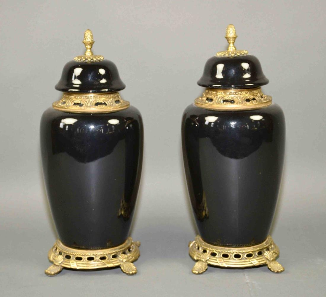 PAIR OF PORCELAIN LIDDED URNS WITH BRASS MOUNTS -