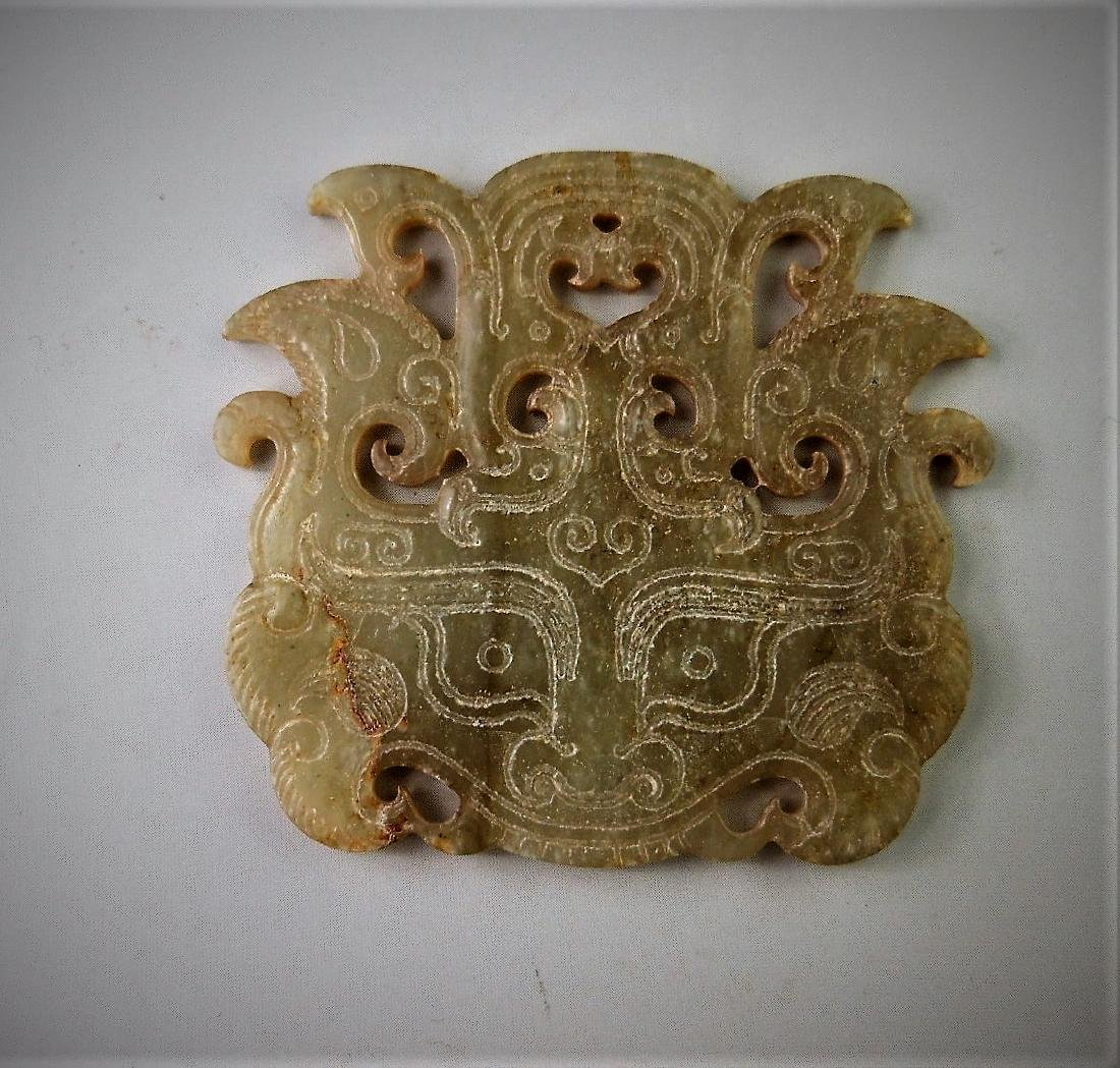 A Chinese archaic jade carved beast mask design pendant