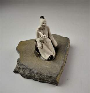 A Chinese small old mud figure on slate