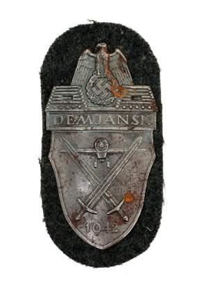 A GERMAN ARMY SLEEVE PATCH DEMJANSK SHIELD ARMY