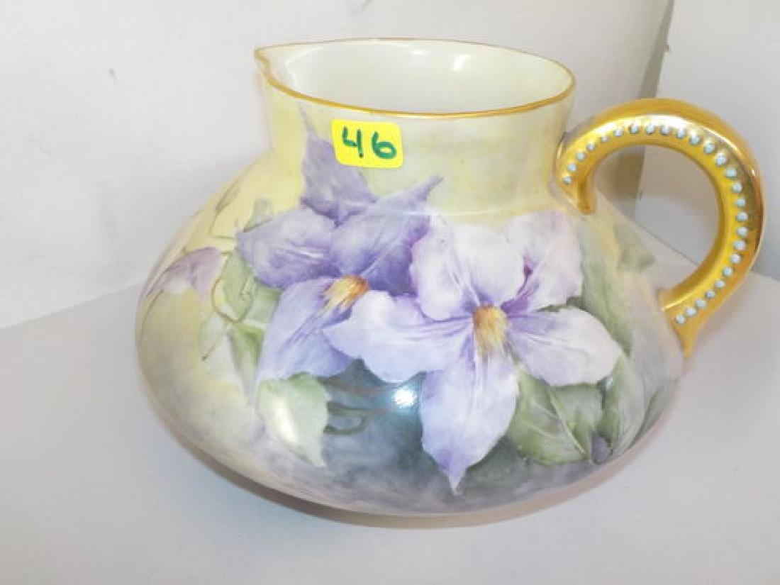 gold handle pitcher with purple flowers bulbous form