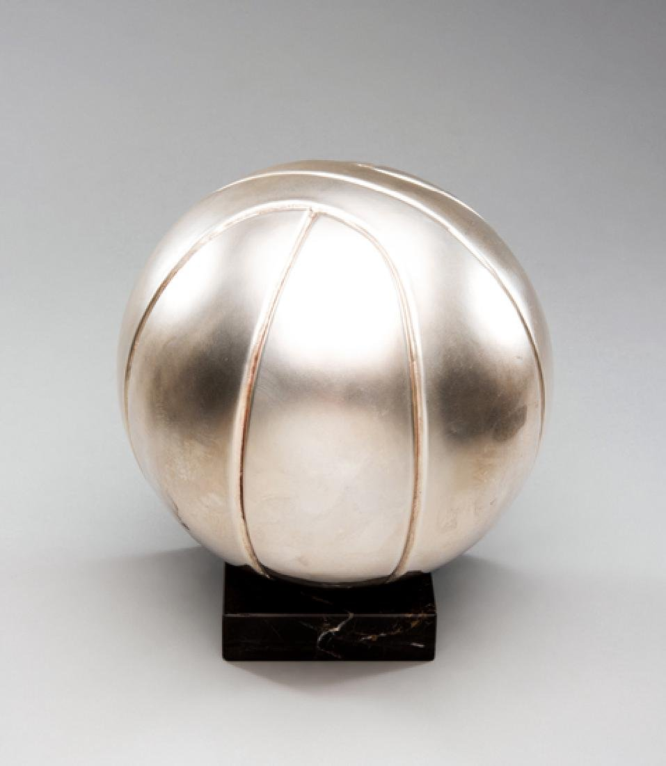 A silver-plated basketball trophy, the ball mounted on