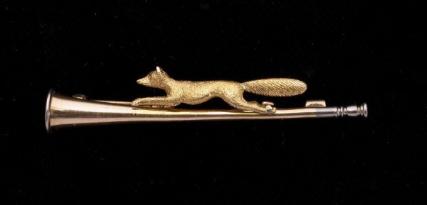 13: A two colour 15ct. gold brooch with a fox and hunti