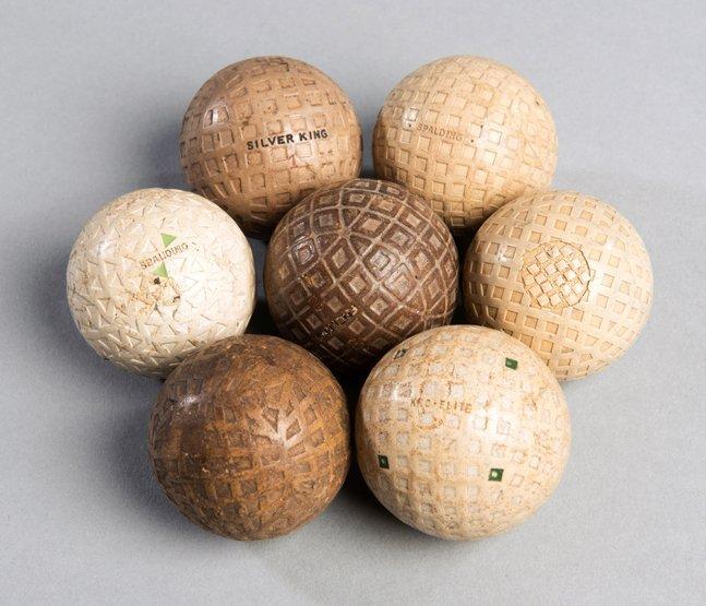Seven golf balls. including a Super Harlequin