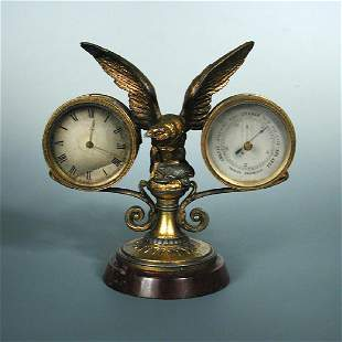 A gilt spelter mounted desk timepiece and aneroid