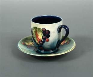 A Moorcroft Leaves and Berries coffee can and saucer