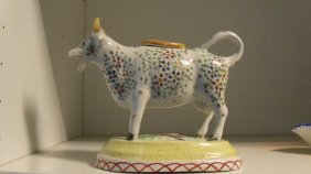 An early 19th century porcellaneous cow creamer and cov
