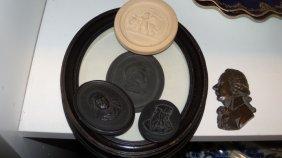 Three basalt portrait profiles, a Danish caneware round