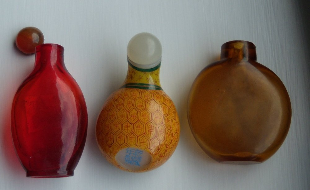 An amber, a ruby and another glass snuff bottle and two