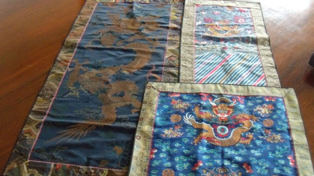 Three gold thread dragons panels on blue silk grounds,