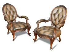 A pair of mid Victorian carved walnut framed armchairs,