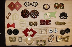 13: A display board of assorted buckles, various dates,