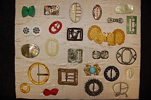 15: A display board of assorted buckles, various dates,