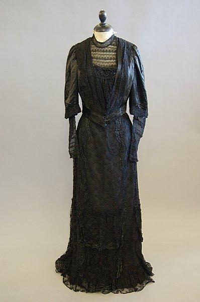 1015: A black satin bodice and skirt, circa 1900, label