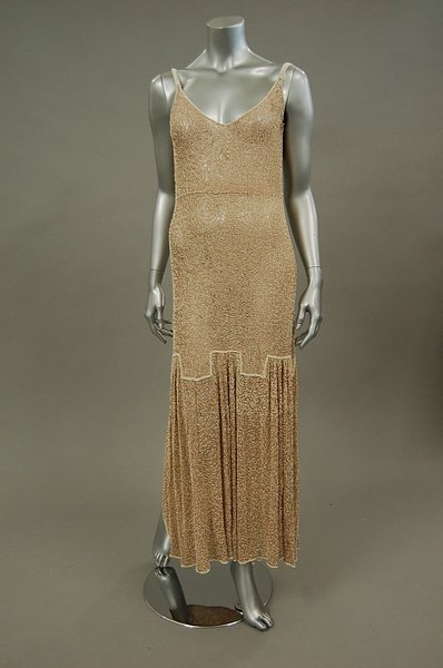 14: A beige lace and white beaded evening gown, circa 1