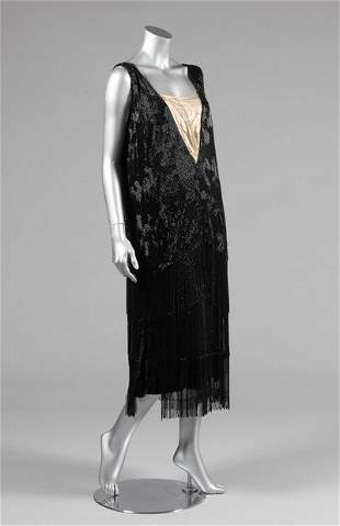 A black beaded flapper dress, mid 1920s, the ground