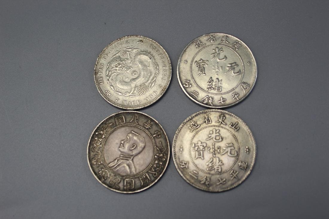 Four Chinese silver coins.