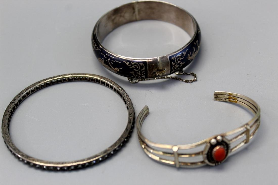 Three sterling silver bangles. One with red coral