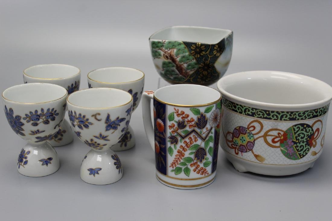 A group of Asian porcelain bowls and cups.