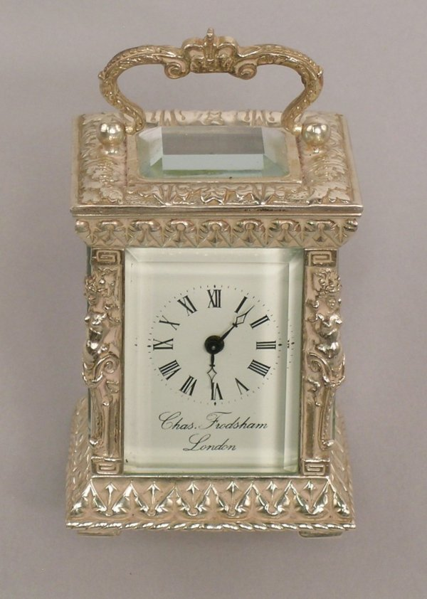 19: A small cast silver mantle timepiece, the white dia
