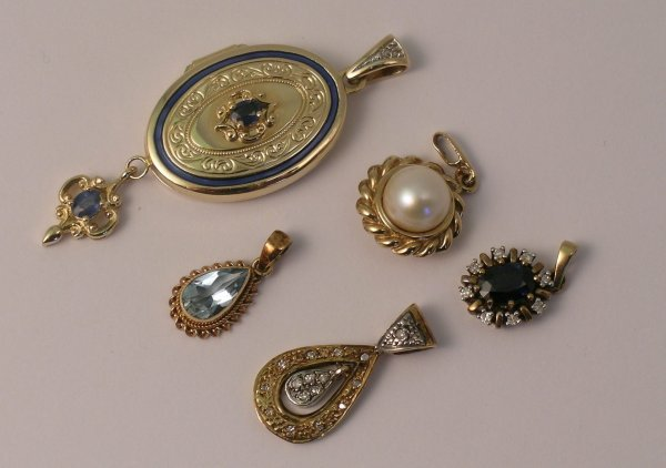 15C: A selection of five pendants to include; a sapphir