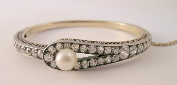 157B: A diamond and untested pearl set hinged bangle, c