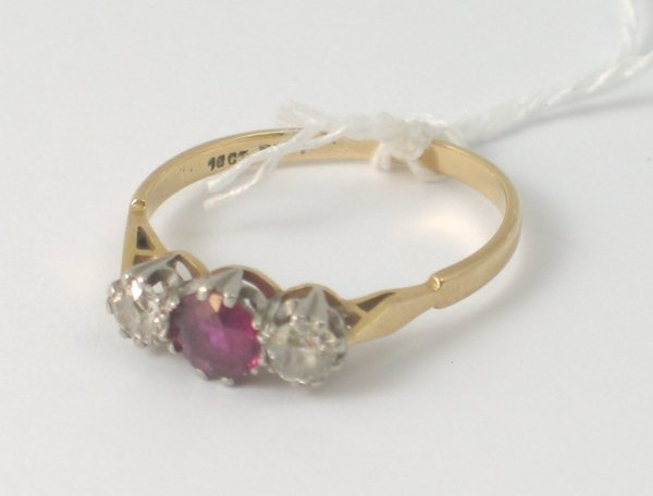 10B: A ruby and diamond three stone ring, the central r