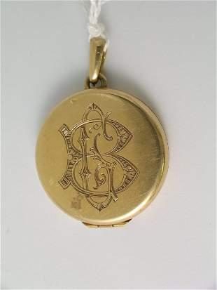 A circular yellow locket, monogrammed 'CB', unmark