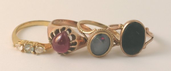 21B: A collection of four rings to include; a cabochon