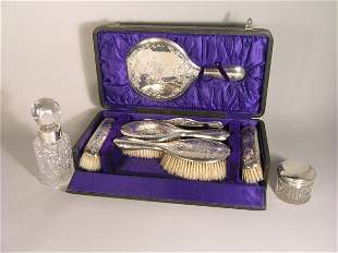 A cased silver backed dressing table set, Williams
