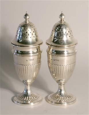 A near pair of silver sugar casters, London 1909 an