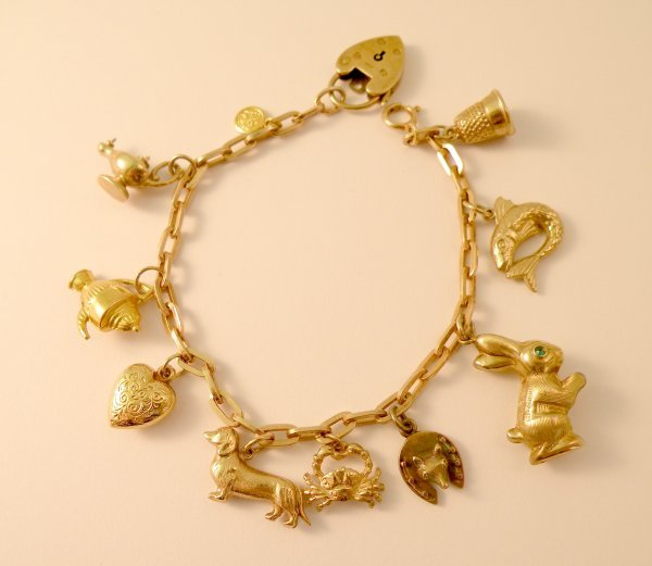 9C: A 9ct gold bracelet with attached charms, the oval