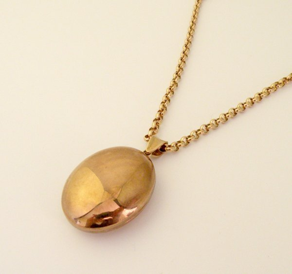 15C: A 9ct rose gold oval locket and chain, the plain o
