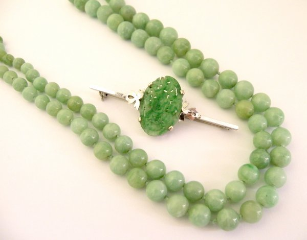 18C: A jadeite bead necklace and brooch, the single str