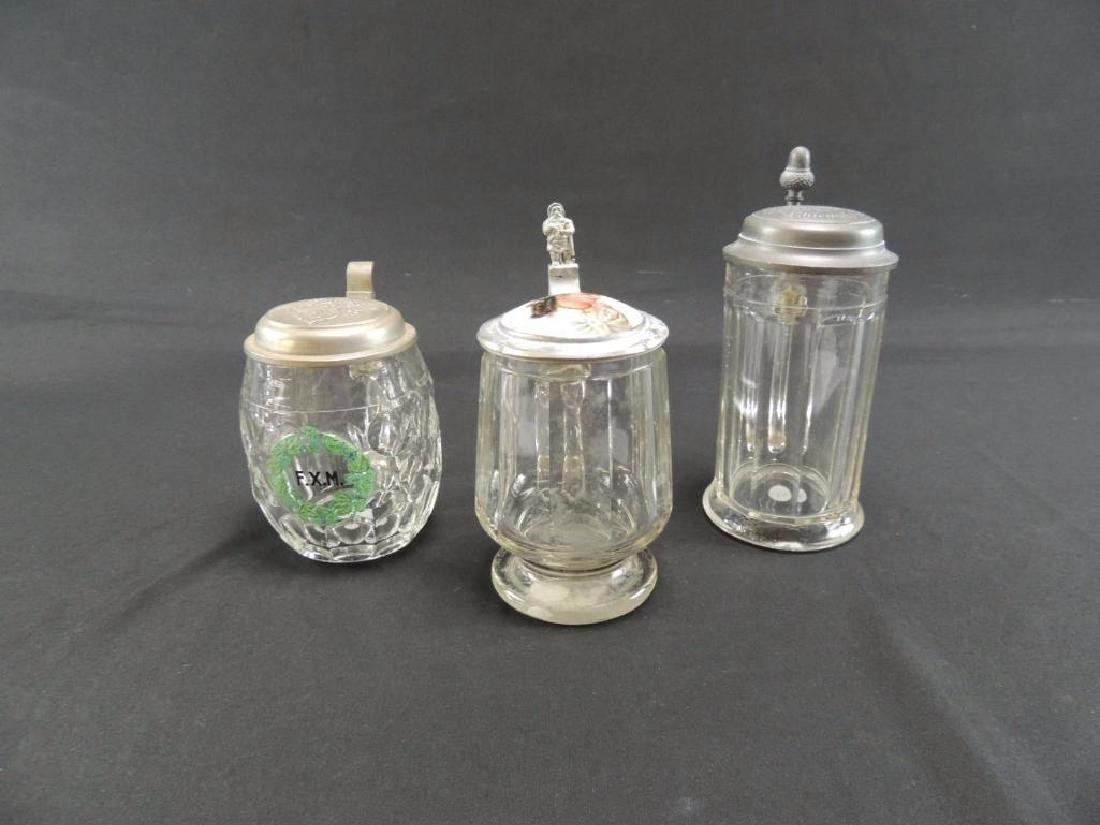 Group of three antique clear glass steins