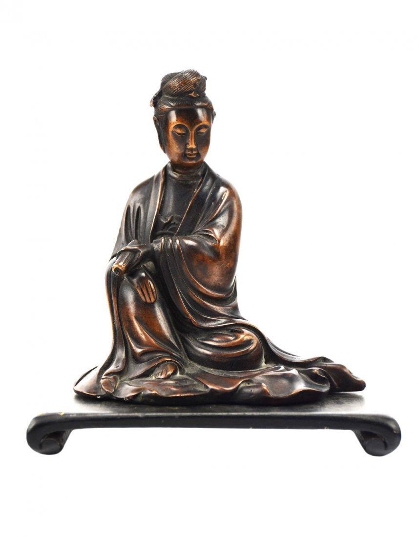 A Seated Quan Yin Figure in Bronze